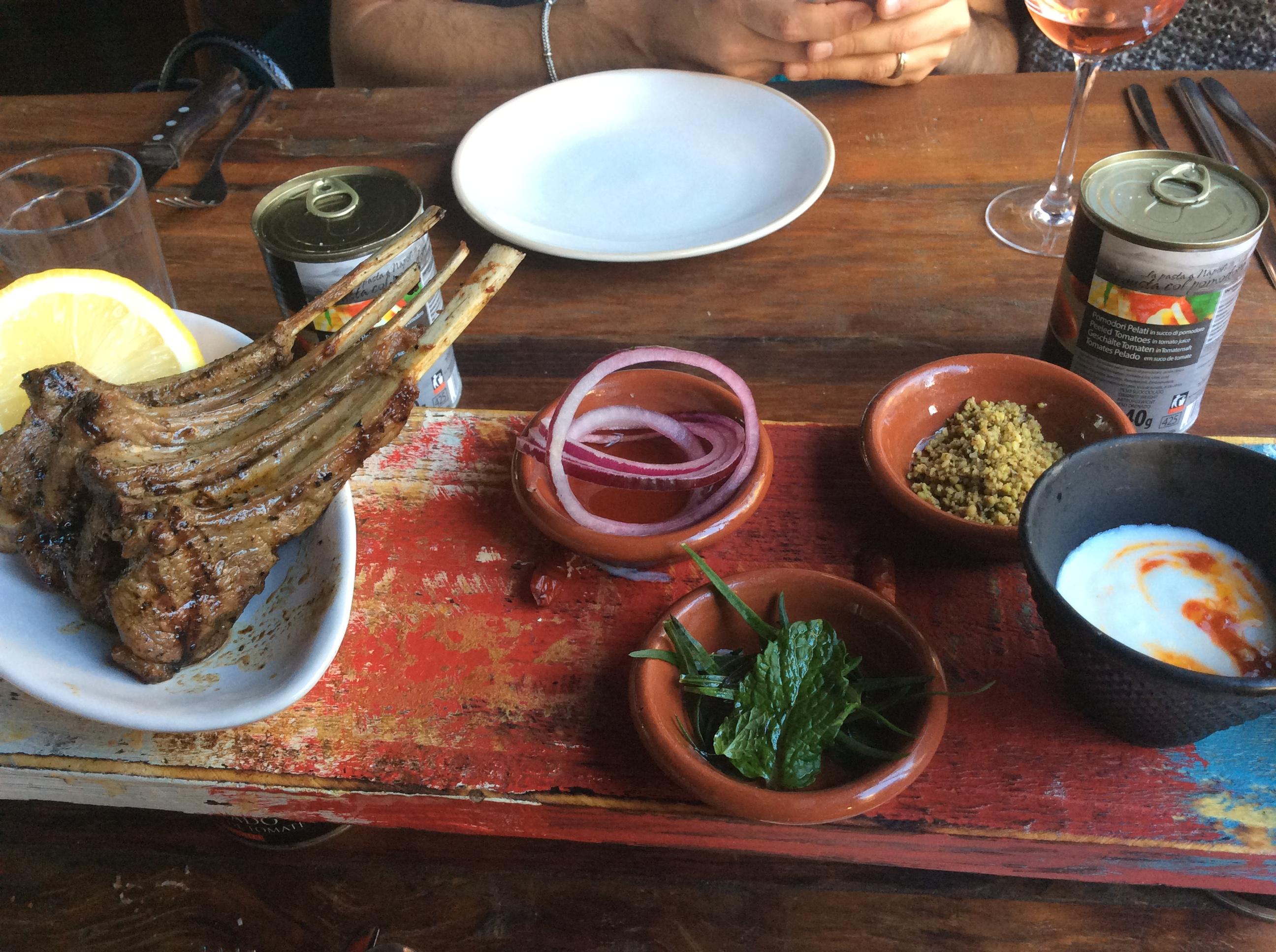 Costeletas de cordeiro Grelhada servidas com picles de cebolas roxa, nozes tostadas, ervas frescas & iogurte cítrico